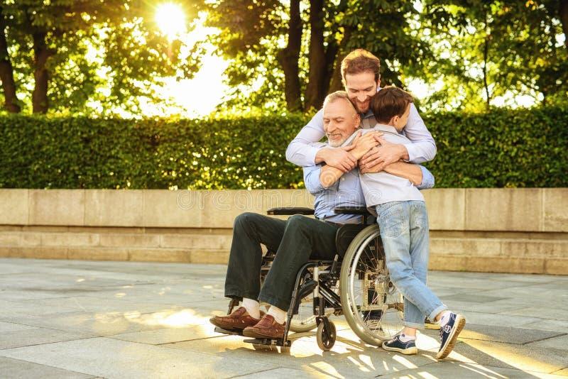 家庭会议 一个人和男孩来看在公园坐轮椅的他们的祖父 库存照片