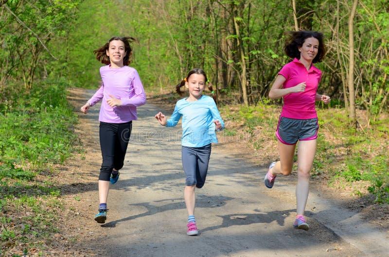 家庭体育、愉快的活跃跑在森林里的母亲和孩子 库存图片