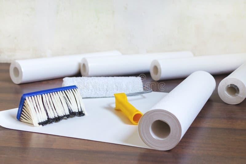 家庭修理、墙纸卷和刷子的准备在地板上 库存图片