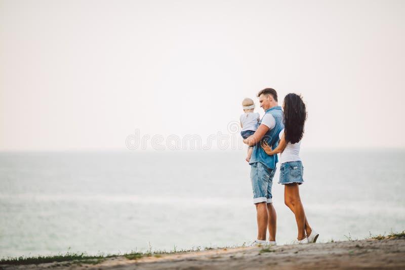 家庭假日本质上 三,妈妈,爸爸,女儿站立与在峭壁俯视的海的后面的一年 拿着hild的人  库存照片