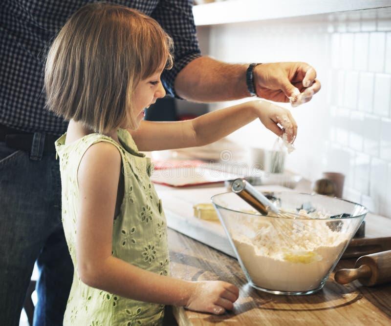 家庭做曲奇饼的父亲女孩学会烘烤概念 库存图片