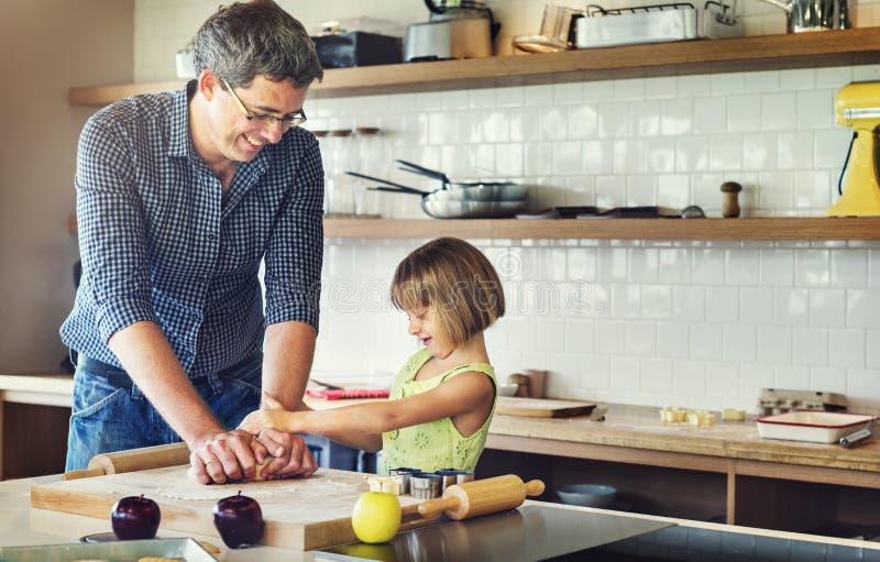 家庭做曲奇饼的父亲女孩学会烘烤概念 免版税库存图片