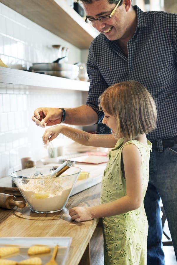 家庭做曲奇饼的父亲女孩学会烘烤 免版税库存照片