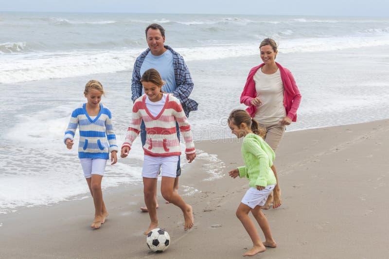 家庭做父母踢海滩足球橄榄球的孩子 图库摄影
