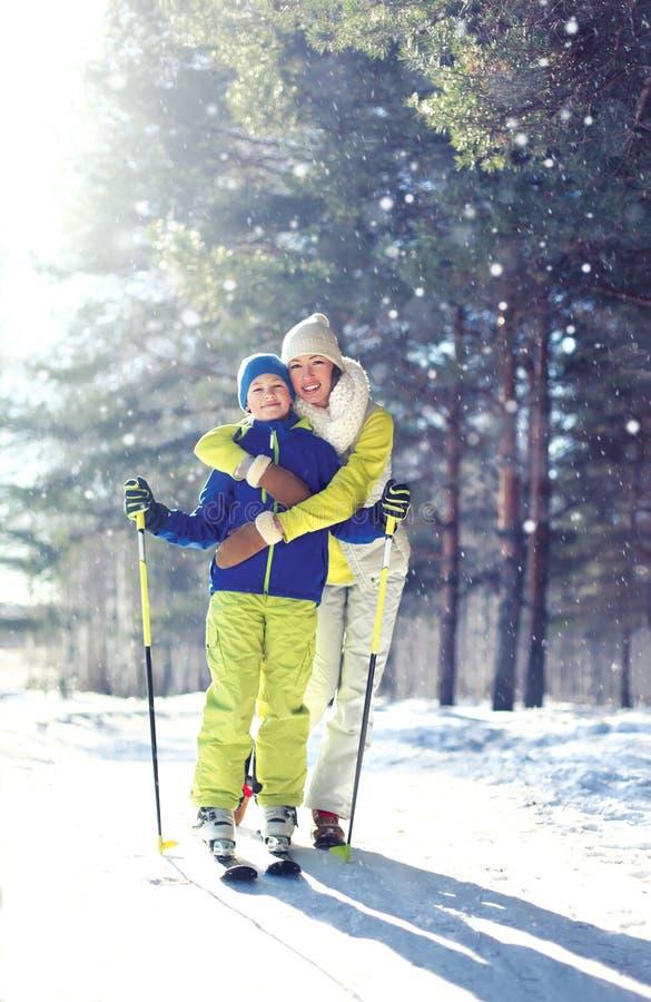 家庭健康生活方式!母亲和儿子孩子去滑雪在冬天森林里 库存照片