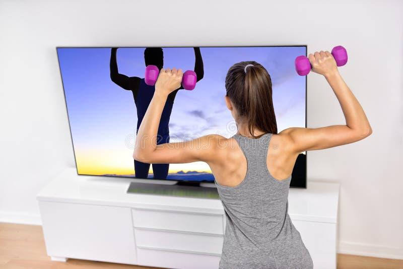 家庭健身妇女力量训练看着电视 免版税库存照片