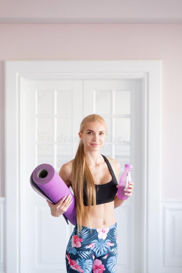 家庭健身 画象年轻人炫耀妇女 健身席子和净水瓶 免版税库存图片