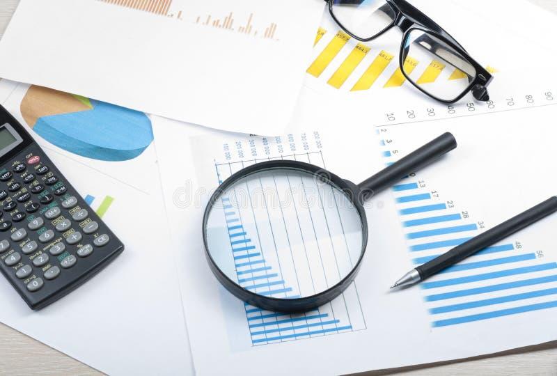 家庭储蓄,预算概念 图、玻璃、笔、计算器和放大镜在木办公室桌上 免版税图库摄影