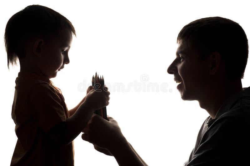 家庭关系剪影,父亲给儿童颜色铅笔 免版税库存照片