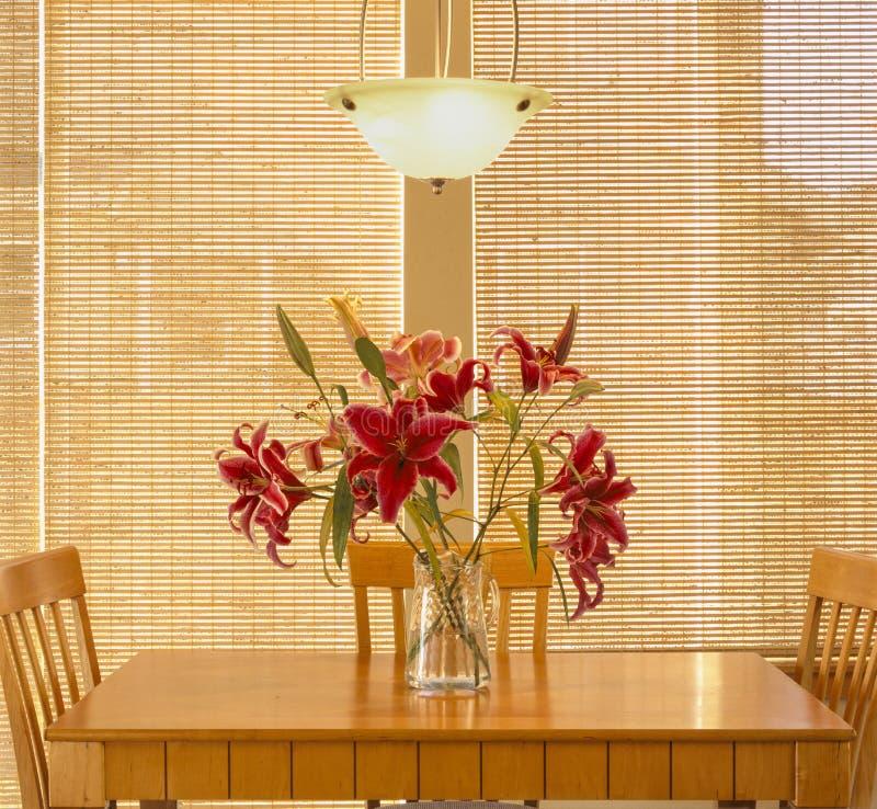 家庭内部有木桌的厨房餐厅和椅子、灯具、鲜花和自然窗罩窗帘 库存图片