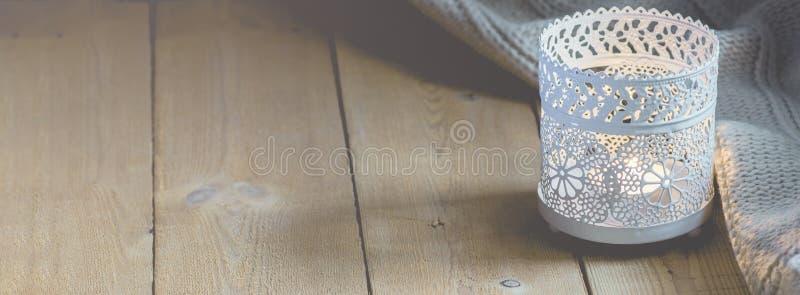 家庭内部网站升蜡烛白色被编织的毛线衣的长的横幅在窗口的板条木表上 舒适冬天秋天晚上 库存图片