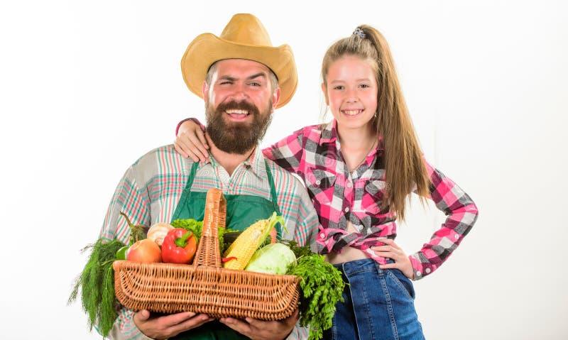 家庭农厂有机菜 有孩子的人有胡子的土气农夫 父亲农夫或花匠有女儿举行篮子的 免版税库存图片