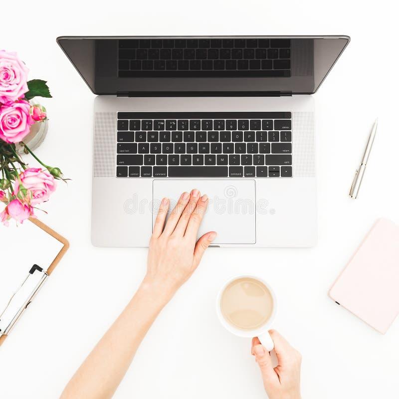家庭办公室书桌 妇女工作区用女性手、膝上型计算机、桃红色玫瑰花束和日志在白色背景 平的位置 顶视图 库存照片