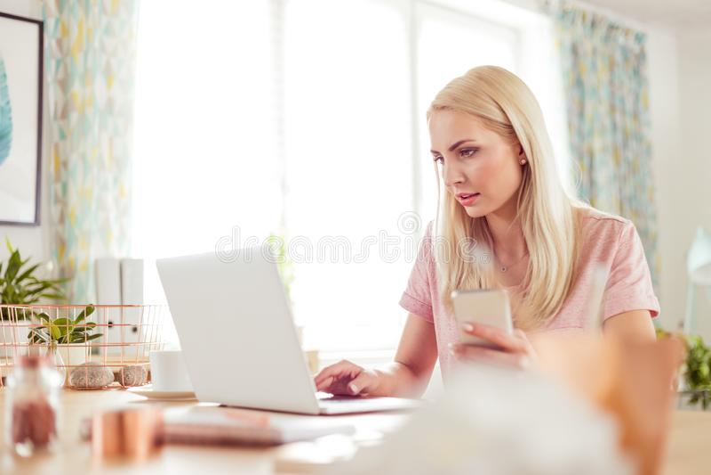 家庭办公室,研究膝上型计算机的繁忙的年轻女人 库存照片