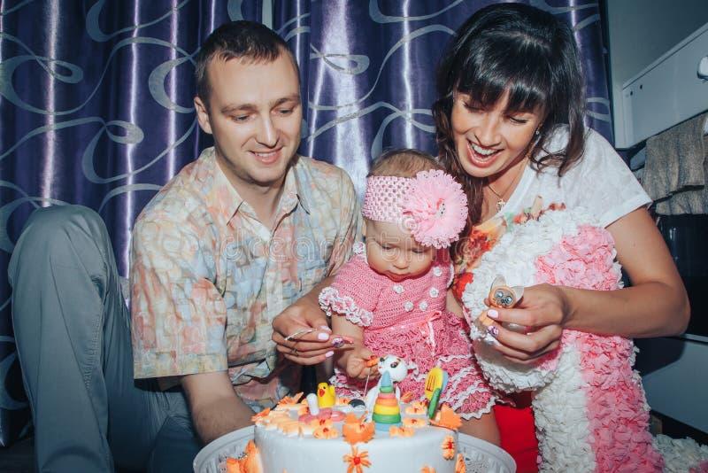 家庭包括父亲、母亲和女儿庆祝生日一岁的女孩 库存图片