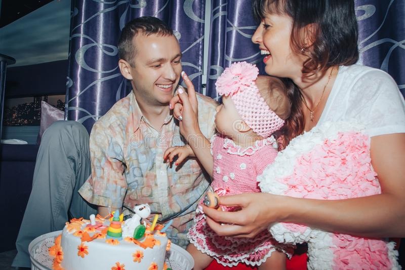 家庭包括父亲、母亲和女儿庆祝生日一岁的女孩 免版税库存照片