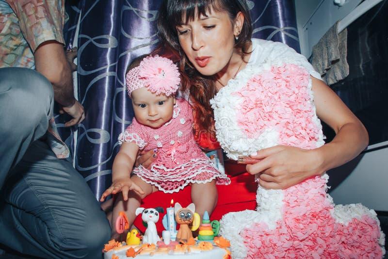 家庭包括父亲、母亲和女儿庆祝生日一岁的女孩 库存照片