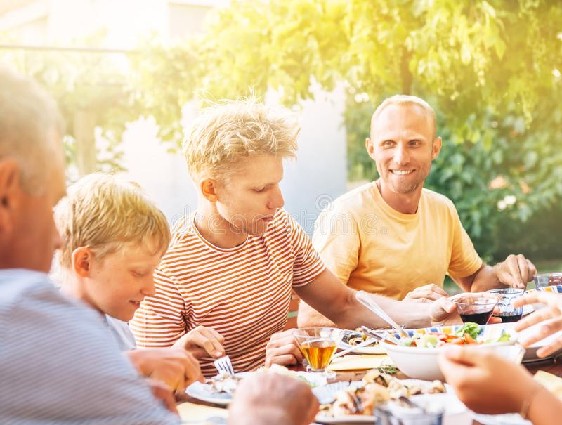 家庭吃在露天的晚餐在夏天庭院 免版税库存照片