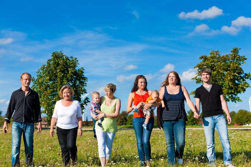 家庭和多代-在草甸的乐趣在夏天 免版税库存图片