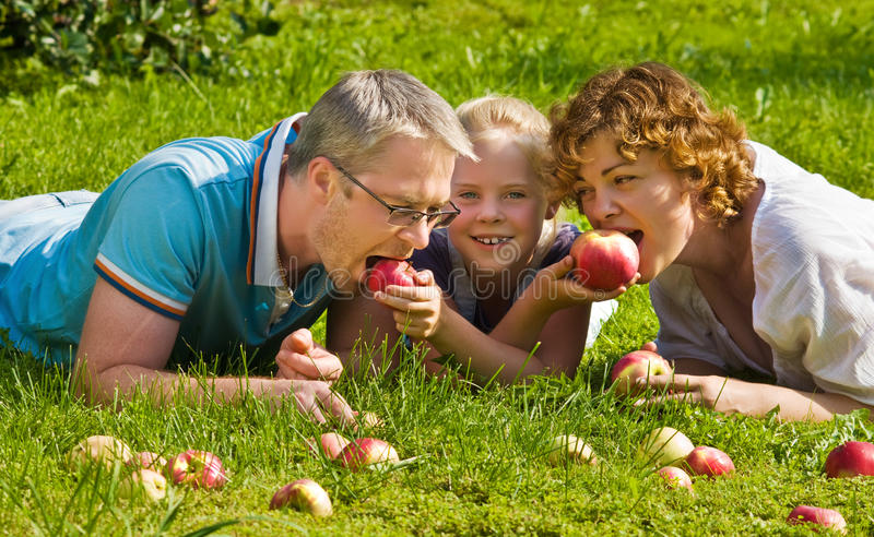 年轻家庭咬住苹果,在草的谎言 图库摄影