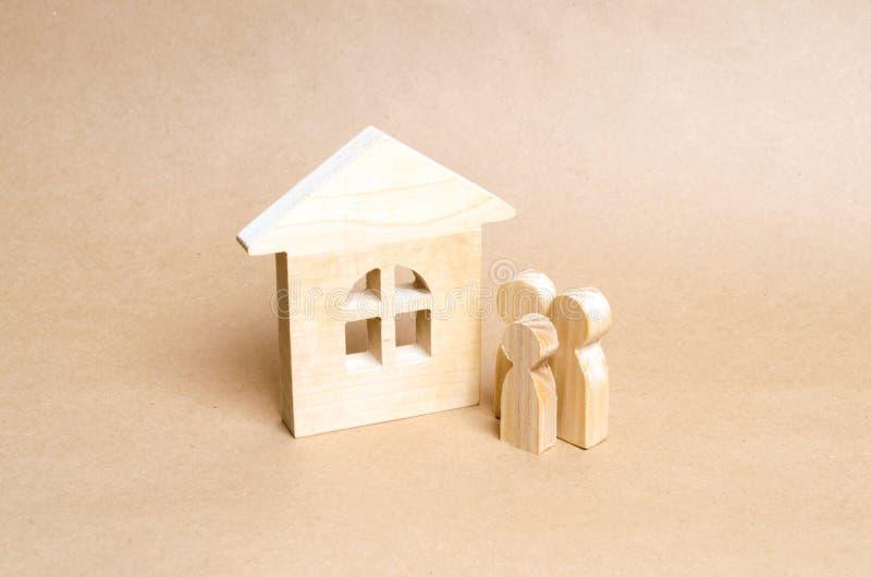 家庭在一个木房子附近站立 两三青年人在他们新的家附近站立 住房购买和销售  免版税库存照片