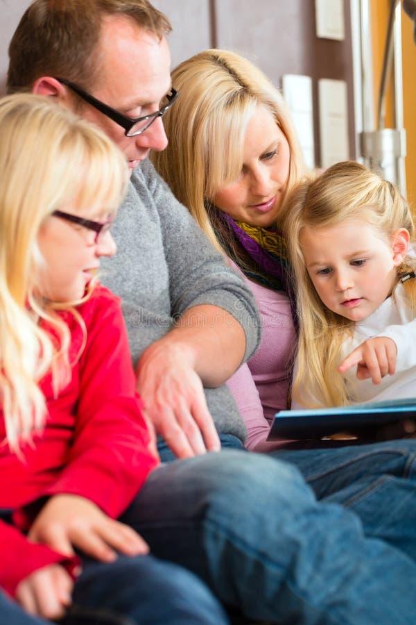 家庭在书的读书故事在沙发在家 免版税库存图片
