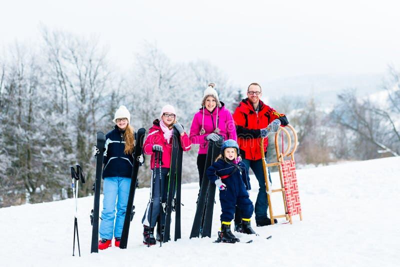家庭在做体育的冬天假期户外 免版税库存照片