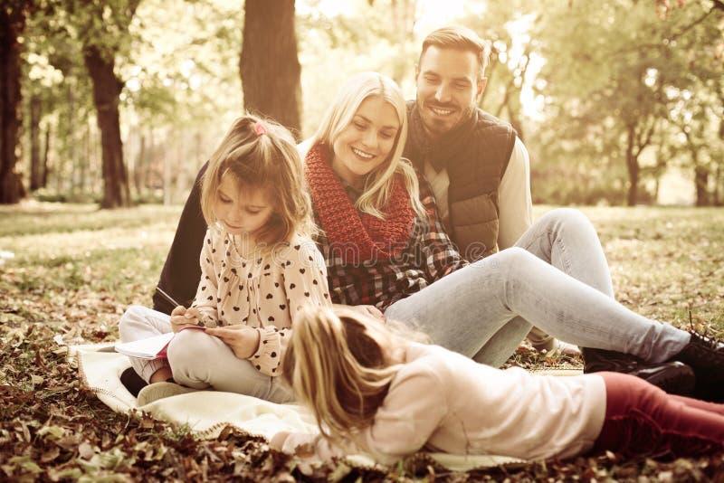 家庭在公园和小女孩一起彩图 免版税库存图片