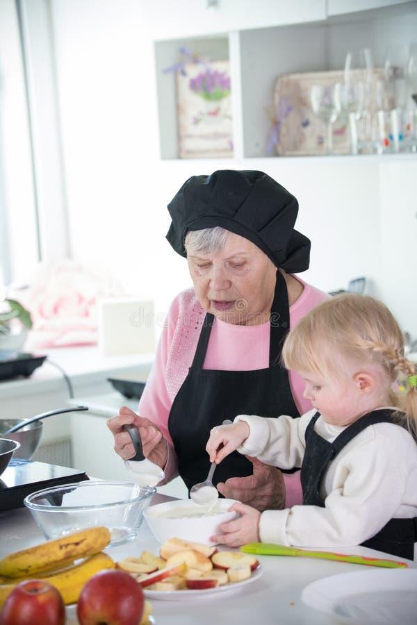 家庭在厨房里 一女孩和她的祖母服务的薄煎饼与酸性稀奶油 免版税库存图片