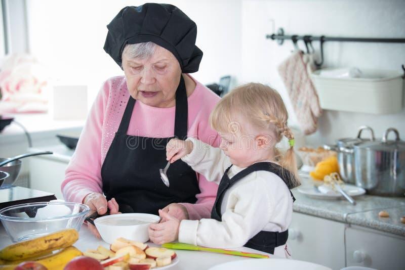 家庭在厨房里 拿着匙子的女孩 免版税库存照片