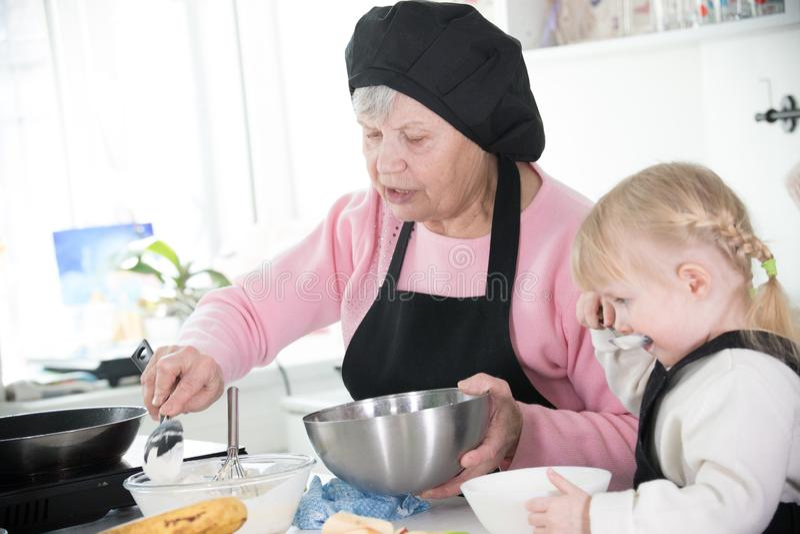 家庭在厨房里 拿着碗和飞奔的祖母 库存图片