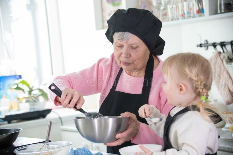 家庭在厨房里 拿着碗的祖母 库存图片
