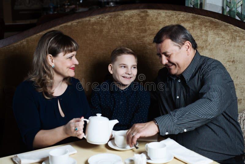 家庭在咖啡馆一起来了 妈妈,爸爸,儿子饮料茶 他们一起是愉快的 幸福家庭午餐概念 免版税库存照片