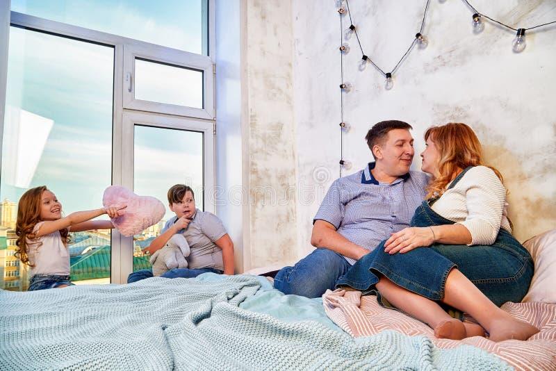 家庭在家一起消费时间在床屋子里 库存图片