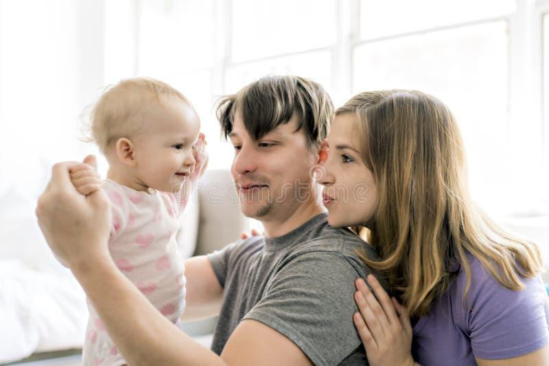 家庭在家获得与婴孩的乐趣沙发的 库存照片