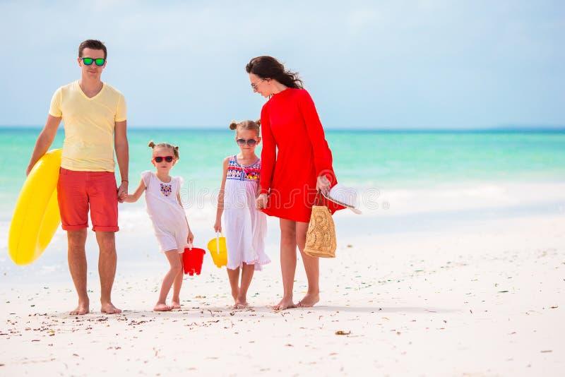 年轻家庭在度假 愉快的父亲、的母亲和获得他们逗人喜爱的孩子乐趣他们的夏天海滩假日 库存图片