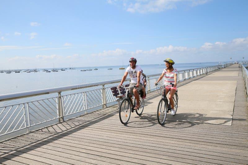 家庭在桥梁的骑马自行车 库存图片