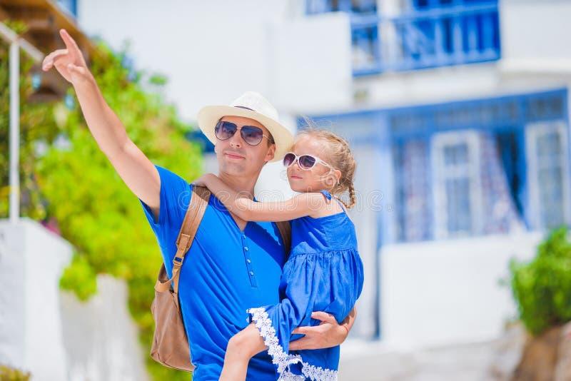 家庭在欧洲 愉快的父亲和小可爱的女孩在夏天希腊语的米科诺斯岛假期 库存照片