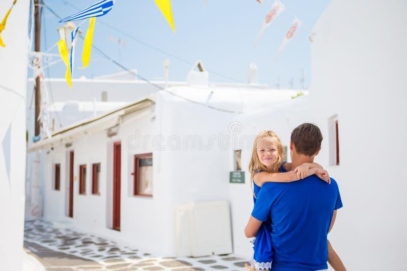 家庭在欧洲 愉快的父亲和小可爱的女孩在夏天希腊语期间的米科诺斯岛假期 免版税库存照片