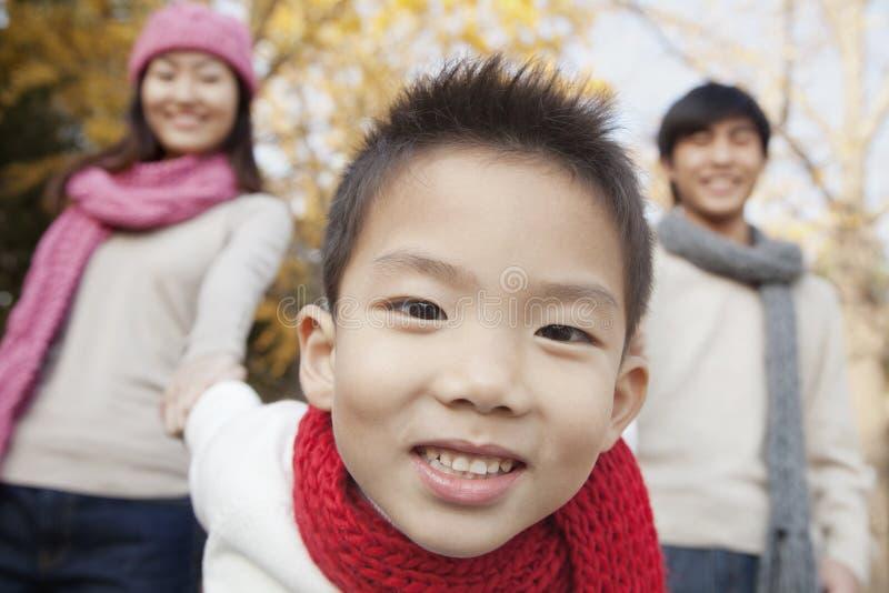 年轻家庭在秋天的享用一个公园 免版税库存照片