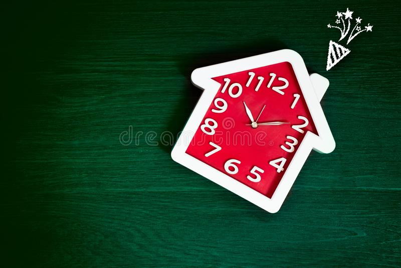 家庭在绿色地板背景的形状红色时钟与庆祝烟花象 幸福生活和家庭观念 内部和对象 免版税图库摄影