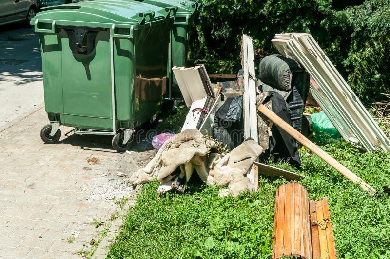 家庭在街道上的垃圾投掷的家具衣橱和窗口在城市在塑料大型垃圾桶附近装乱丢和pollu于罐中 免版税图库摄影
