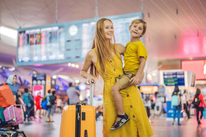 家庭在飞行前的机场 等待的母亲和的儿子上在现代国际终端登机口  免版税库存照片