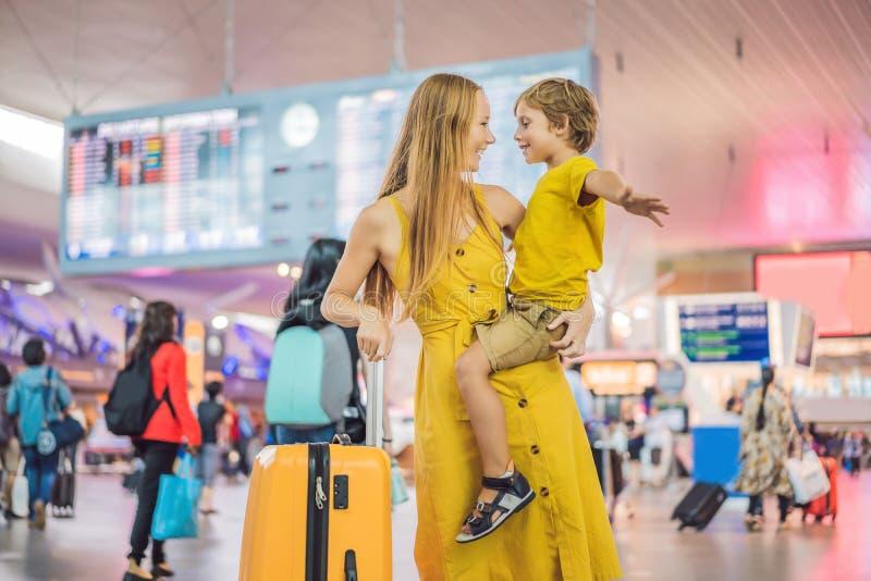 家庭在飞行前的机场 等待的母亲和的儿子上在现代国际终端登机口  库存图片