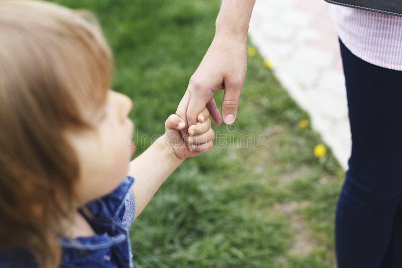 家庭场面、结合在一起使手的特写镜头父母和婴孩 有想知道的面孔的逗人喜爱的小孩男孩,查寻,拿着妈咪` s飞翅 免版税库存照片