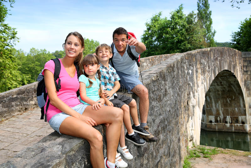 家庭坐一座石桥梁 库存照片
