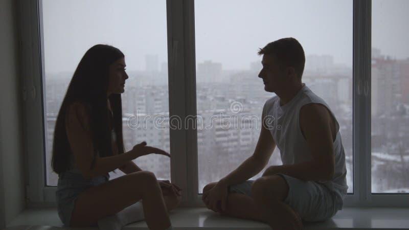 家庭夫妇坐窗台,谈话,情感地争论和姿势示意 库存照片