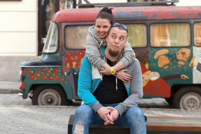 家庭夫妇特写镜头临近五颜六色的绘画老汽车或吉普赛人嬉皮搬运车 在享用在momen的爱的愉快的浪漫年轻夫妇 免版税库存图片