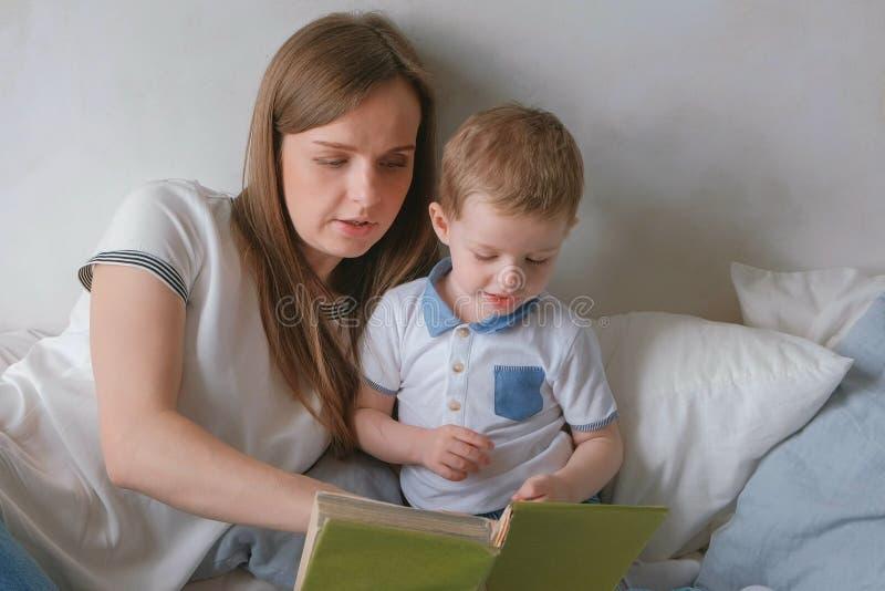 家庭妈妈和儿子小孩读了放置在床的书 家庭读书时间 库存照片