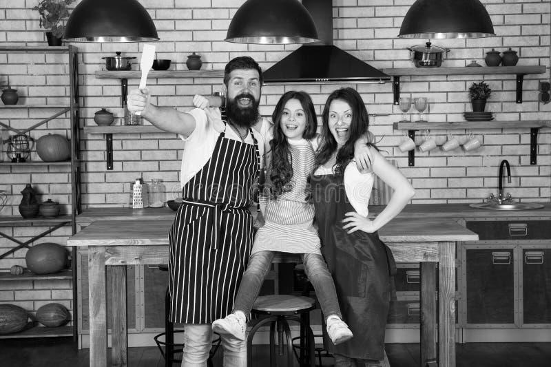家庭妈妈爸爸和女儿穿戴围裙在厨房里站立 r 准备可口膳食 r 免版税图库摄影